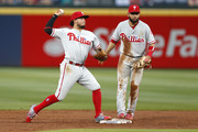 Shortstop Freddy Galvis #13 of the Philadelphia Phillies turns a double play while second baseman Andres Blanco #4 looks on in the second inning during the game against the Atlanta Braves at Turner Field on May 12, 2016 in Atlanta, Georgia.