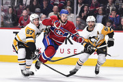 Jonathan Drouin #92 of the Montreal Canadiens skates through Sidney Crosby #87 and Kris Letang #58 of the Pittsburgh Penguins during the NHL game at the Bell Centre on October 13, 2018 in Montreal, Quebec, Canada.  The Montreal Canadiens defeated the Pittsburgh Penguins 4-3 in a shootout.