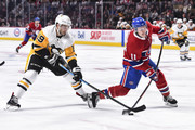 Derick Brassard #19 of the Pittsburgh Penguins tries to challenge Brendan Gallagher #11 of the Montreal Canadiens as he takes a slap shot during the NHL game at the Bell Centre on October 13, 2018 in Montreal, Quebec, Canada.