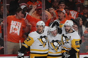 Jake Guentzel #59 of the Pittsburgh Penguins (c) celebrates his goal at 12:58 of the third period against the Philadelphia Flyers and is joined by Sidney Crosby #87 (l) and Kris Letang #58 (r) in Game Six of the Eastern Conference First Round during the 2018 NHL Stanley Cup Playoffs at the Wells Fargo Center on April 22, 2018 in Philadelphia, Pennsylvania. The Penguins defeated the Flyers 8-5 to win the series 4-2.
