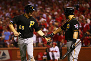 Justin Morneau #66 celebrates with Russell Martin #55 of the Pittsburgh Pirates as he scores on a single by Pedro Alvarez #24 in the seventh inning against the St. Louis Cardinals during Game Five of the National League Division Series at Busch Stadium on October 9, 2013 in St Louis, Missouri.
