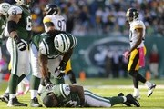 Running back Chris Ivory #23 of the New York Jets lies on the ground in pain as teammates guard Brian Winters #67 and linebacker DeMario Davis #56 look over him during the second half against the Pittsburgh Steelers at MetLife Stadium on October 13, 2013 in East Rutherford, New Jersey. The Steelers defeated the Jets 19-6.