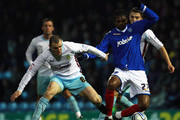 Dean Marney of Burnley battles with Kanu of Portsmouth during the npower Championship match between Portsmouth and Burnley at Fratton Park on January 25, 2011 in Portsmouth, England.