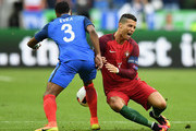 Cristiano Ronaldo (R) of Portugal is challenged by Patrice Evra (L) of France during the UEFA EURO 2016 Final match between Portugal and France at Stade de France on July 10, 2016 in Paris, France.