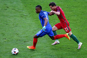 Patrice Evra of France and Cedric Soares of Portugal compete for the ball during the UEFA EURO 2016 Final match between Portugal and France at Stade de France on July 10, 2016 in Paris, France.