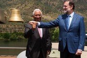 """Spanish Prime Minister Mariano Rajoy (R) and his Portuguese counterpart Antonio Costa both ring the bell of the """"MS Douro Elegance"""" ship on the first day of the XXIX Portugal - Spain summit in La Fregeneda, on May 29, 2017. / AFP PHOTO / MIGUEL RIOPA"""