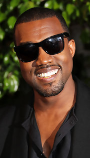 Kanye was all smiles at the premiere of 'Runaway'. He completed his dapper suit with classic wayfarer shades.