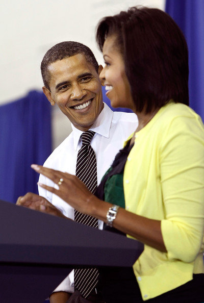 "AFP OUT U.S. President Barack Obama (L) laughs as first lady Michelle Obama does a little dance while making remarks during a United We Serve event at Fort McNair June 25, 2009 in Washington, DC. Helping to fill 10,000 backpacks for children of military servicemen and women, the first family stuffed copies of ""The Lightning Thief,"" by Rick Riordan, and ""The Penderwicks,"" by Jeanne Birdsall into backpacks along with food items and a personal letter from the president and the first lady."