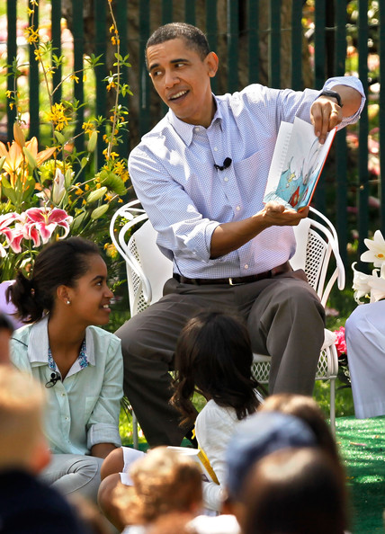 "With his daughter Sasha Obama (C), 8, and Malia Obama (L), 11, at his feet, President Barack Obama reads ""Green Eggs and Ham,"" by Dr. Suess, during the Easter Egg Roll at the White House April 5, 2010 in Washington, DC.  About 30,000 people are expected to attend attended the 132-year-old tradition of rolling colored eggs down the South Lawn of the White House."