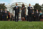 (L-R) U.S. President Barack Obama, first lady Michelle Obama and Vice President Joe Biden listen to Taps after observing a moment of silence to mark the 13th anniversary of the 9/11 attacks on the South Lawn of the White House September 11, 2014 in Washington, DC. Obama and the first lady will travel to the Pentagon later today for another memorial ceremony.
