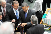 Australian opposition leader Tony Abbott watches as U.S. President Barack Obama inspects ties presented to him by the only Aboriginal MP Ken Wyatt (R), in the House of Representatives chamber at Parliament House on the second day of his 2-day visit to Australia, on November 17, 2011 in Canberra, Australia. The President will this afternoon fly to Darwin to lay a wreath at the USS Peary Memorial, and visit the RAAF base, where US Army Air Force units were established during World War II.