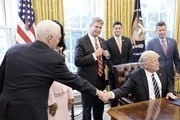 "(AFP-OUT) U.S. President Donald Trump shakes hands with Vice-President Mike Pence  after signing H.J. Res. 41 in the Oval Office of the White House on February 14, 2017 in Washington, DC. The resolution nullifies a rule in the Dodd-Frank Act that ""requires resource extraction issuers to disclose payments made to governments for the commercial development of oil, natural gas, or minerals."" Also pictured are Rep. Bill Huizenga (R-MI) (3rd R) and House Speaker Paul Ryan (R-WI) (2nd R)."