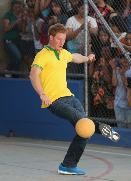 Prince Harry plays football as he visits the ACER Charity for disadvantaged children on June 25, 2014 in Sao Paulo, Brazil.  Prince Harry is on a four day tour of Brazil that will be followed by two days in Chile.