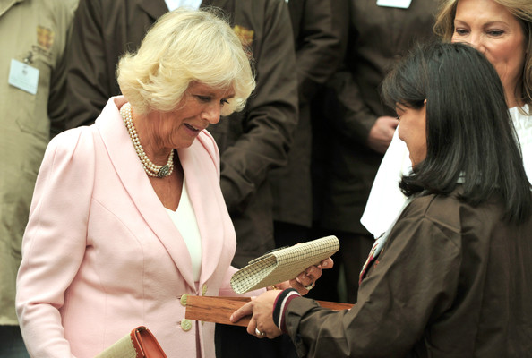 Camilla, Duchess of Cornwall is presented with a a clutch bag by teacher Magly Palacios during a visit to Escuela de Artes Y Oficios Arts and Crafts School on October 29, 2014 in Bogota, Colombia. The Royal Couple are on a four day visit to Colombia as part of a Royal tour to Colombia and Mexico. After fifty years of armed conflict in Colombia the theme for the visit is Peace and Reconciliation.