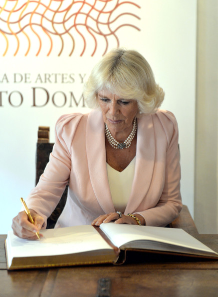 Camilla, Duchess of Cornwall signs the visitor's book as she visits Escuela de Artes Y Oficios Arts and Crafts School on October 29, 2014 in Bogota, Colombia. The Royal Couple are on a four day visit to Colombia as part of a Royal tour to Colombia and Mexico. After fifty years of armed conflict in Colombia the theme for the visit is Peace and Reconciliation.