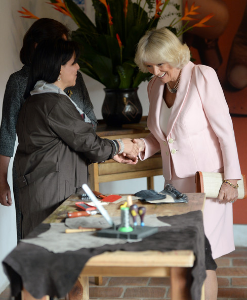 Camilla, Duchess of Cornwall meets Magly Palacios, a teacher who made a clutch bag for the Duchess, during a visit to Escuela de Artes Y Oficios Arts and Crafts School on October 29, 2014 in Bogota, Colombia. The Royal Couple are on a four day visit to Colombia as part of a Royal tour to Colombia and Mexico. After fifty years of armed conflict in Colombia the theme for the visit is Peace and Reconciliation.