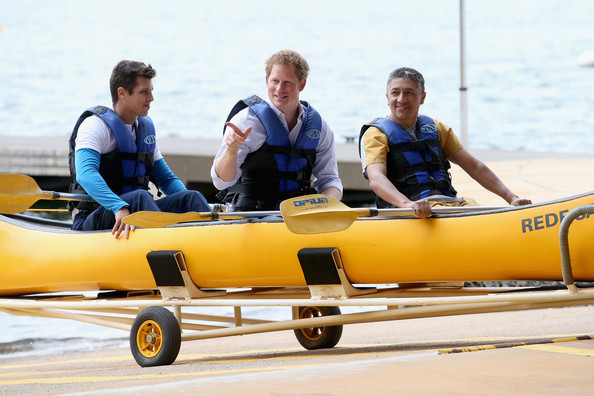 Prince Harry canoes with patient Israel Lima (R) and an instructor from the Rede Sarah Hospital for Nerological Rehabilitation injuries as he takes part in a canoe therapy session on Lake Paranoa on June 23, 2014 in Brasilia, Brazil.  Prince Harry is on a four day tour in Brazil that will be followed by two days in Chile.