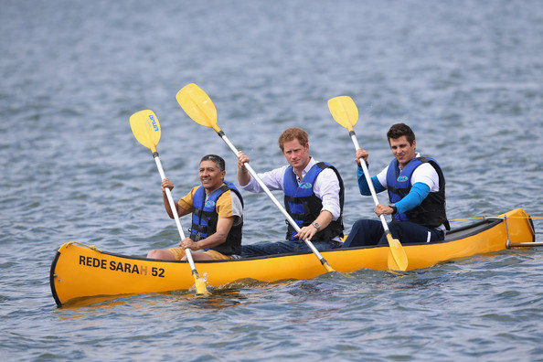 Prince Harry canoes with patient Israel Lima (L) and an instructor from the Rede Sarah Hospital for Nerological Rehabilitation injuries as he takes part in a canoe therapy session on Lake Paranoa on June 23, 2014 in Brasilia, Brazil.  Prince Harry is on a four day tour in Brazil that will be followed by two days in Chile.