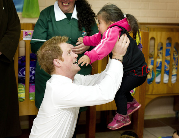 Prince Harry picks up a toddler as he visits kindergarten of indigenous children a on June 27, 2014 in Santiago, Chile.  Prince Harry is on a three day tour of Chile after visiting Brazil.