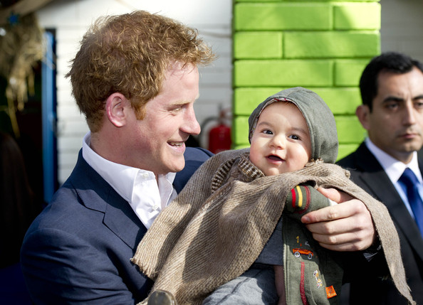 Prince Harry holds young Matias Gonzalez as he visits a the Sagrada Familia kindergarten, a kindergarden of indigenous children on June 27, 2014 in Santiago, Chile.  Prince Harry is on a three day tour of Chile after visiting Brazil.