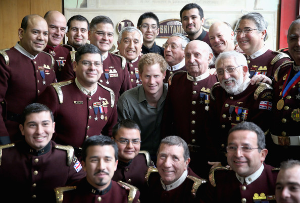 Prince Harry poses with firemen from Valpariso Firestation on June 28, 2014 in Valpariso, Chile. Firefighters from Valpariso were involved in dealing with the devastating forest fires that hit the area in April. Prince Harry is on a three day tour of Chile after visiting Brazil.