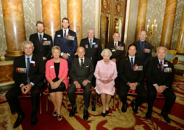 Queen Elizabeth II and Prince Philip, Duke of Edinburgh (front row, centre) sit with Australian and New Zealand members of the Victoria and George Cross Association, before a reunion reception in the picture Gallery of Buckingham Palace on October 28, 2014 in central London.