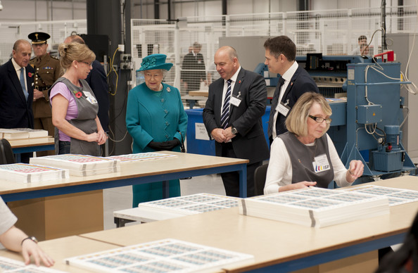 Queen Elizabeth II is shown stamp quality control by MD Paul White & production Manager Andrew Bannister during an official visit to International Security Printers to view their work on specialist postage stamps on October 30, 2014 in Wolverhampton, England.