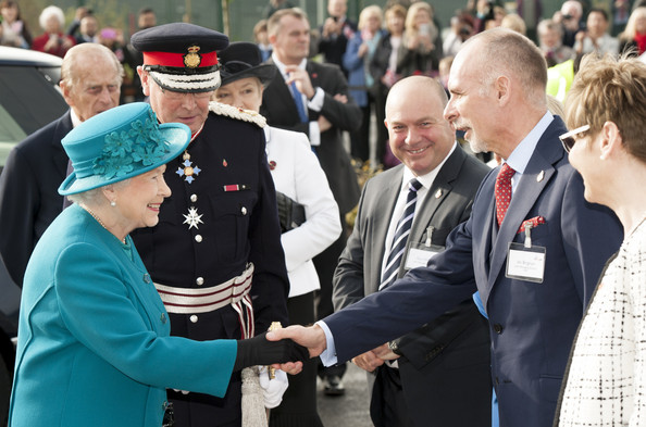 Queen Elizabeth II is greeted by MD Ian Brigham during an official visit to International Security Printers to view their work on specialist postage stamps on October 30, 2014 in Wolverhampton, England.