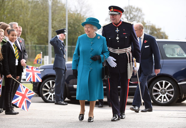 Queen Elizabeth II (L) and Prince Philip, Duke of Edinburgh (R) are greeted by the Lord Lieutenant of Staffordshire Ian Dudson (C) as they arrive at the new Jaguar Land Rover Engine Manufacturing Centre in Wolverhampton to officially open the plant, on October 30, 2014 in Wolverhampton.