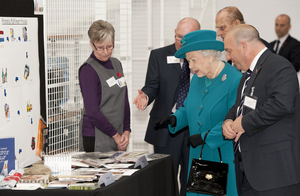 Queen Elizabeth II and Prince Philip, Duke of Edinburgh are shown examples of stamps produced at the factory by MD Paul White during an official visit to International Security Printers to view their work on specialist postage stamps on October 30, 2014 in Wolverhampton, England.