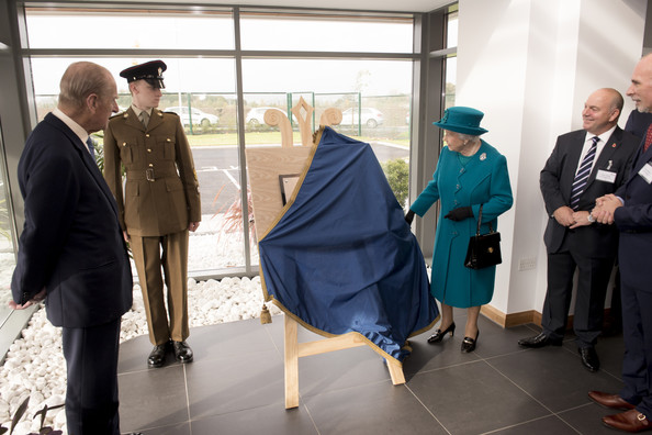 Queen Elizabeth II and Prince Philip, Duke of Edinburgh unveil a plaque during an official visit to International Security Printers to view their work on specialist postage stamps on October 30, 2014 in Wolverhampton, England.