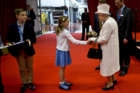Queen Elizabeth II is given a posie of flowers by Jessica Barrell, 9, from Gilwern Primary School following a visit to International Greetings UK Ltd at the Penallta Industrial Estate in Ystrad Mynach during her visit to south west Wales on April 30, 2014 in Ystrad Mynach, Wales.