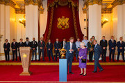 Prince Harry, Queen Elizabeth II and Prince Philip, Duke of Edinburgh view the Webb Ellis Trophy at a Rugby World Cup reception at Buckingham Palace on October 12, 2015 in London, United Kingdom.