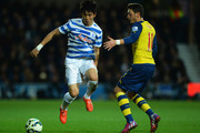 Yoon Suk-Young of QPR evades Mesut Oezil of Arsenal during the Barclays Premier League match between Queens Park Rangers and Arsenal at Loftus Road on March 4, 2015 in London, England.
