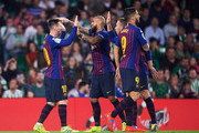 Lionel Messi of FC Barcelona celebrates with his teammates Arturo Vidal and Arthur Melo of FC Barcelona after scoring his team's second goal during the La Liga match between Real Betis Balompie and FC Barcelona at Estadio Benito Villamarin on March 17, 2019 in Seville, Spain.