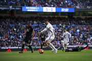 Cristiano Ronaldo (2ndL) of Real Madrid CF competes for the ball with David Rodrguez Lombn (L) of Granada CF during the La Liga match between Real Madrid CF and Granada CF at Estadio Santiago Bernabeu on January 7, 2017 in Madrid, Spain.