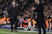 Dortmund's Dutch head coach Peter Bosz (L) stand on the sideline beside Real Madrid's French coach Zinedine Zidane during the UEFA Champions League group H football match Real Madrid CF vs Borussia Dortmund at the Santiago Bernabeu stadium in Madrid on December 6, 2017. / AFP PHOTO / JAVIER SORIANO