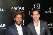 Actors André Holland (L) and Clive Owen attend a private viewing and dinner for Art For Love: 32 Photographers Interpret The Iconic Moncler Maya Jacket hosted by Remo Ruffini, Moncler chairman and Kevin Robert Frost, amFAR CEO New York Public Library - Celeste Bartos Forum on September 10, 2015 in New York City.