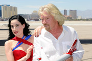 Burlesque artist Dita Von Teese (L) and Founder and President of Virgin Group Sir Richard Branson appear with a model Virgin Atlantic Airways plane on the tarmac at McCarran International Airport June 15, 2010 in Las Vegas, Nevada. Branson is celebrating his British airline's 10th anniversary of flying between London and Las Vegas.