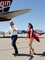 Founder and President of Virgin Group Sir Richard Branson (L) and burlesque artist Dita Von Teese walk across the tarmac at McCarran International Airport after posing for photos on a Virgin Atlantic Airways 747-400 aircraft June 15, 2010 in Las Vegas, Nevada. Branson is celebrating his British airline's 10th anniversary of flying between London and Las Vegas.