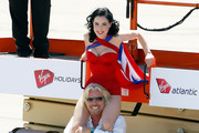 Founder and President of Virgin Group Sir Richard Branson helps burlesque artist Dita Von Teese get down from a lift as they pose with a Virgin Atlantic Airways 747-400 aircraft at McCarran International Airport June 15, 2010 in Las Vegas, Nevada. Branson is celebrating his British airline's 10th anniversary of flying between London and Las Vegas.