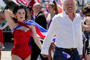 Burlesque artist Dita Von Teese (L) and Founder and President of Virgin Group Sir Richard Branson walk across the tarmac at McCarran International Airport after posing for photos on a Virgin Atlantic Airways 747-400 aircraft June 15, 2010 in Las Vegas, Nevada. Branson is celebrating his British airline's 10th anniversary of flying between London and Las Vegas.