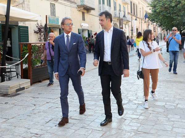 FIGC 120 Years Exhibition In Matera [photograph,people,snapshot,fashion,pedestrian,suit,tourism,footwear,street fashion,event,michele uva,head coach,roberto mancini,matera,italy,figc 120 years exhibition]