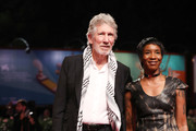 """Roger Waters and unknown guest walks the red carpet ahead of the """"Roger Waters Us + Them"""" screening during the 76th Venice Film Festival at Sala Darsena on September 06, 2019 in Venice, Italy."""