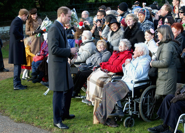 Catherine, Duchess of Cambridge, Prince Harry and Prince William, Duke of Cambridge stop to chat to members of the public as he leaves the Christmas Day Service at Sandringham Church on December 25, 2014 in King's Lynn, England.