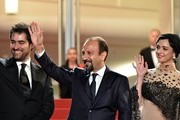 """(FromL) Iranian actor Shahab Hosseini, Iranian director Asghar Farhadi and Iranian actress Taraneh Alidoosti wave as they arrive on May 21, 2016 for the screening of the film """"The Salesman (Forushande)"""" at the 69th Cannes Film Festival in Cannes, southern France.  / AFP / ALBERTO PIZZOLI"""