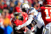 De'Anthony Thomas #13 of the Kansas City Chiefs runs the ball as Marcus Gilchrist #38 of the San Diego Chargers defends in the first quarter at Arrowhead Stadium on December 28, 2014 in Kansas City, Missouri.