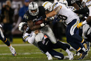 Running back Latavius Murray #28 of the Oakland Raiders is tackled by line backer Manti Te'o #50 and free safety Eric Weddle #32 of the San Diego Chargers in the second quarter at O.co Coliseum on December 24, 2015 in Oakland, California.
