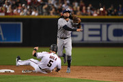 Freddy Galvis #13 of the San Diego Padres turns a double play during the fifth inning as Alex Avila #5 of the Arizona Diamondbacks slides into second base at Chase Field on September 3, 2018 in Phoenix, Arizona.