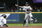 Freddy Galvis #13 of the San Diego Padres gets the force out on Nelson Cruz #23 of the Seattle Mariners and makes the throw to first for the double play in the first inning at Safeco Field on September 12, 2018 in Seattle, Washington.